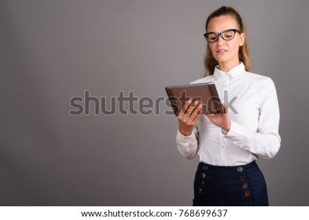 Studio shot of young beautiful businesswoman against gray background