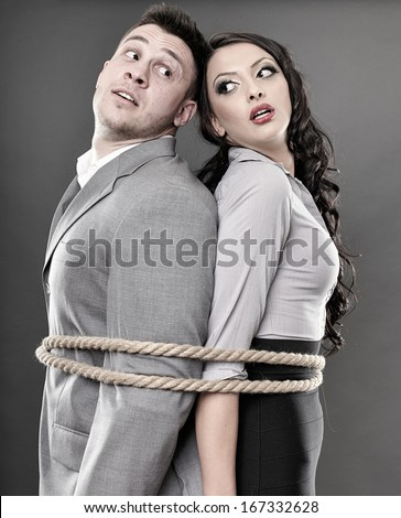 Studio shot of young couple back to back tied with a rope - stock photo