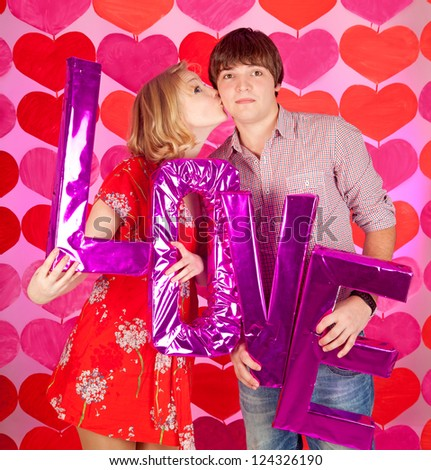 studio shot of young couple in love over colorful background - stock photo
