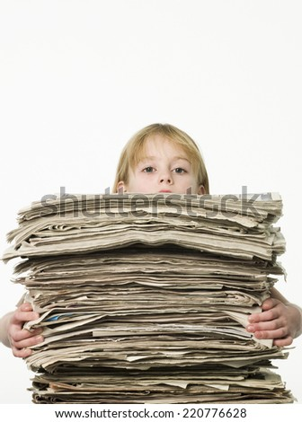 Studio shot of young girl on white background carrying an enormous pile of newspapers - stock photo