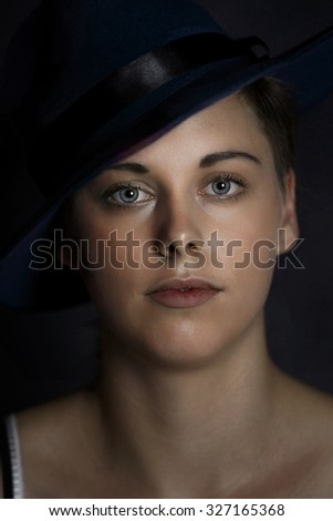 Studio shot of young girl wearing hat. Plain black background.