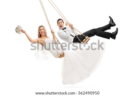 Studio shot of young groom and a bride swinging on wooden swings isolated on white background - stock photo