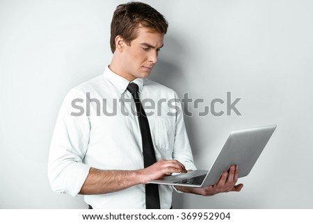 Studio shot of young handsome businessman. Businessman seriously using laptop