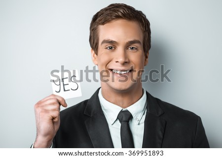 Studio shot of young handsome businessman. Businessman smiling, looking at camera and holding sticker with word yes on it