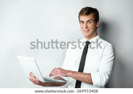 Studio shot of young handsome businessman. Businessman smiling, looking at camera and using laptop