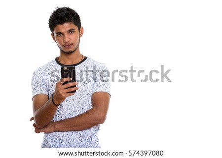 Studio shot of young handsome Indian man holding mobile phone