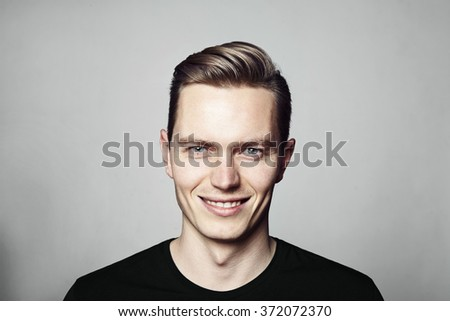 Studio shot of young handsome man. Isolated on white background. Horizontal format, he is looking to the camera, he is wearing a black T-shirt. - stock photo