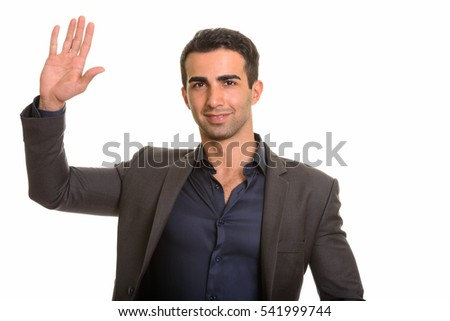 Studio shot of young happy businessman waving hand isolated against white background