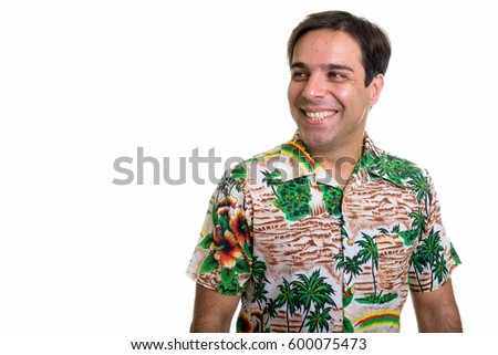 Studio shot of young happy Persian tourist man smiling and thinking while wearing Hawaiian shirt isolated against white background