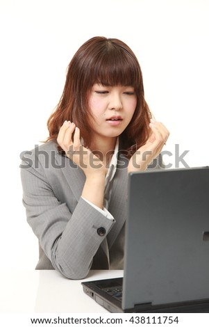 studio shot of young Japanese businesswoman wearing gray suits shocked