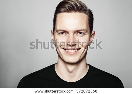 Studio shot of young man smiling to camera. Isolated on white background. Horizontal format, he is looking to the camera, he is wearing a black T-shirt. - stock photo
