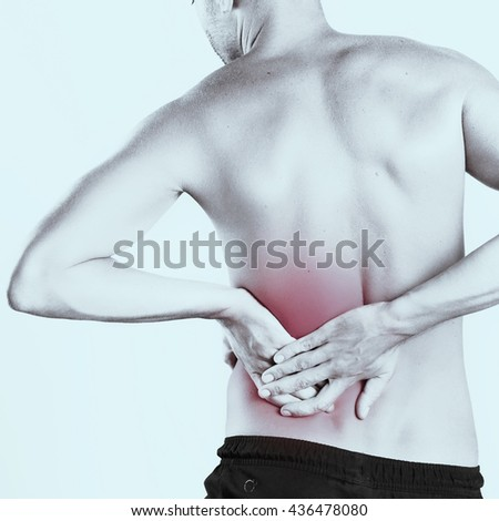 Studio shot of young man with pain in back - stock photo