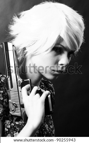 studio shot of young woman holding .44 Magnum handgun on black background