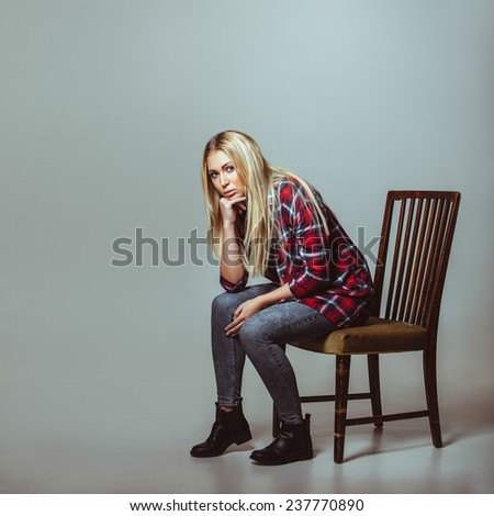 Studio shot of young woman in casual outfit sitting on chair looking at camera. Caucasian female model with copyspace. - stock photo