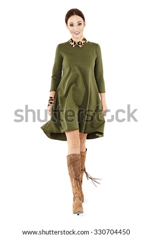 Studio shot of young woman in green dress walking ahead. Isolated on white.  - stock photo