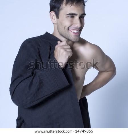 studio shot on isoltaded background portrait of handsome man in bathrobe - stock photo