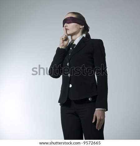 studio shot portrait of a beautiful young blindfold woman in a costume suit - stock photo
