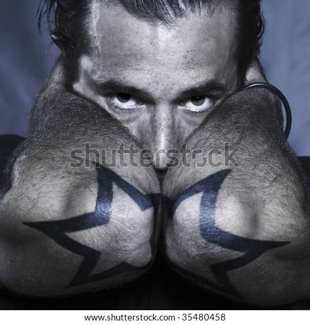 studio shot portrait of a urban stylish man with stars tattoos on his elbows