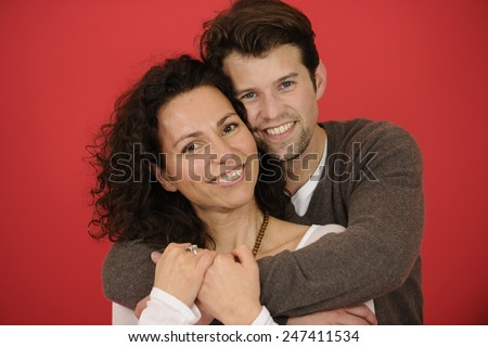 Studio shot: Portrait of happy man and woman on red background  - stock photo