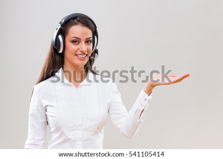 Studio shot portrait of young businesswoman who is holding your advertisement.