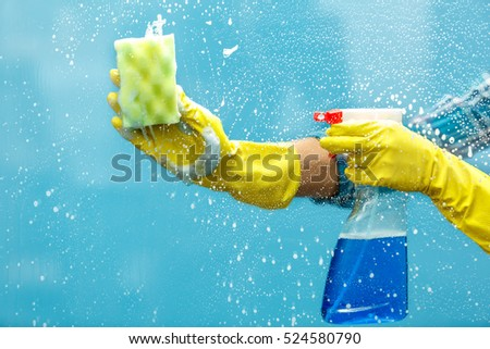 Studio shot through glass of housekeeper. Woman hand with glove holding bottle of spray and using sponge to make window clean. Focus on hand