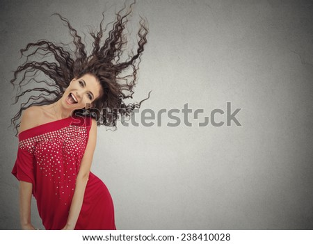 Studio shot young happy laughing playful woman posing in red dress isolated on grey wall  background with copy space. Positive emotion, face expression - stock photo