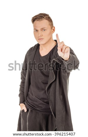 Studio shot young man in black clothes showing one finger. emotions, facial expressions, feelings, body language, signs. image on a white studio background.