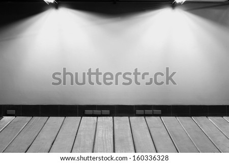 Studio spot lighting over dark background and wood floor - stock photo