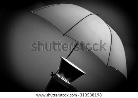 Studio strobe with umbrella for portraits and photographs - stock photo