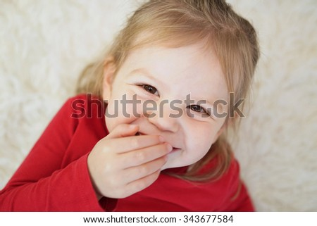 Studio style photo of young girl giggling and showing emotion - stock photo
