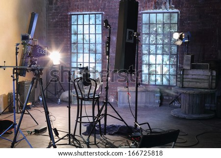 Studio with studio with brick walls and ragged windows, spotlights, camera with special devices for shooting video. - stock photo