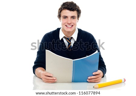 Studious boy preparing for half yearly exams. Holding his notebook and reading - stock photo