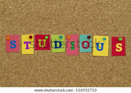 Studious word written on colorful sticky notes pinned on cork board.