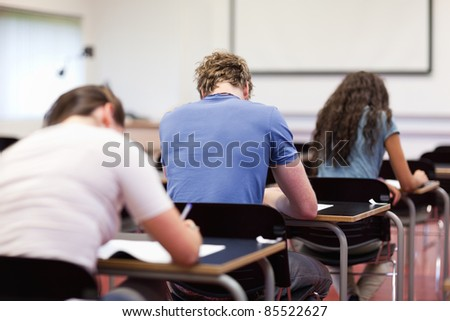 Studious young adults writing in a classroom - stock photo