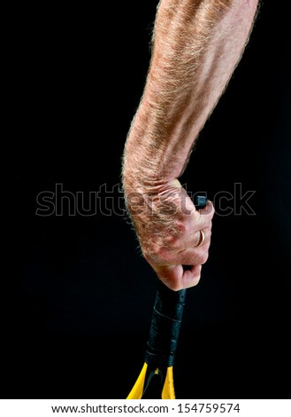 Study, athletic man's arm and hand, holding tennis racquet, showing detail of hairs, veins, tendons, forearm muscles - stock photo