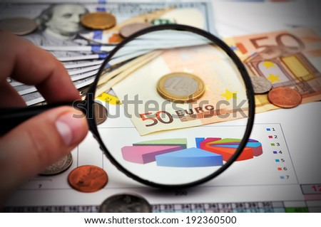study of Euro coin with a magnifying glass - stock photo