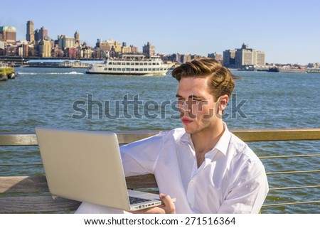 Study Outside. Young blonde, handsome student, wearing white shirt, sitting by river, reading, working on laptop computer. a small boat, big city on far background. Traveler.  - stock photo