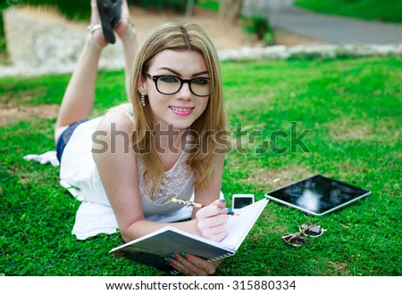 Studying Beautiful Woman Lying Down At The Park Writing On Notebook