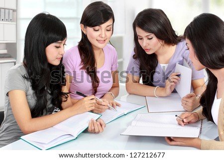 Studying happy young woman reading her book for school together with friends