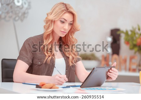 Studying in new age. Young attractive woman looking at digital tablet and making some notes in the notepad while sitting at her work place at home - stock photo