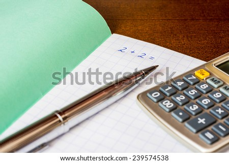 Studying in the school, solving mathematical problems, a pen and  a calculator on the table. Angle view - stock photo