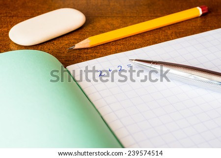 Studying in the school, solving mathematical problems, a pencil and eraser on the table - stock photo