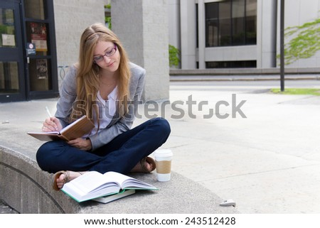 Studying on campus with books and notepad - stock photo