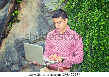 Studying Outside. Wearing red patterned, long sleeve shirt, wristwatch,  a young college student standing against rocks with long green leaves, looking down, reading, working on laptop computer. - stock photo