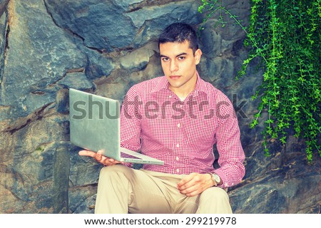 Studying Outside. Wearing red, white patterned shirt, wristwatch, a young college student sitting against rocks with long green leaves on campus, reading, thinking, working on laptop computer.  - stock photo