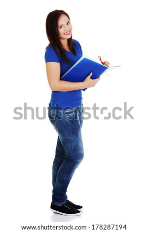 Studying thoughtful young woman reading her notebook for school. - stock photo