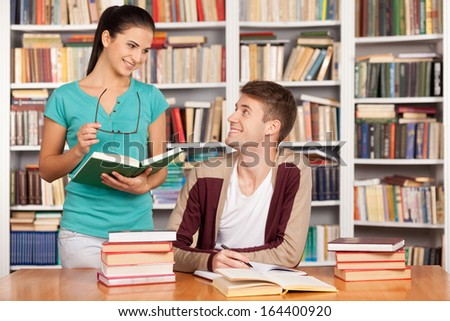 Studying together. Cheerful young man sitting at the desk while beautiful woman standing close to him and holding book - stock photo