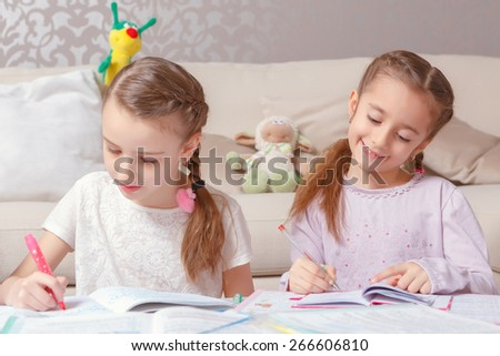 Studying together. Two pretty junior schoolgirls writing with pens and felt tip pens in their note pads sitting in a living room - stock photo