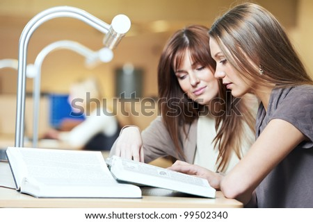 Studying young teenage college student girl  in a library with books in front of book shelves - stock photo