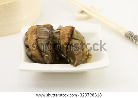 Stuff eggplants with minced meat mix with fish paste. A dim sum style Chinese cuisine prepared as small bite-size portion of food traditionally served in small steamer basket or on small plate. - stock photo